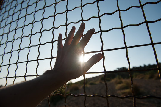 human hand touching fence cage in jail and illegal immigration on sunset