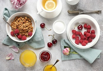 Breakfast table setting with granola and fresh raspberries. Overhead view
