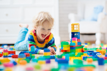 Child playing with toy blocks. Toys for kids. Wall mural