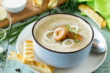 Puree soup mushrooms with croutons in a bowl on a kitchen wooden table. The concept of healthy eating. Diet menu. Copy space.