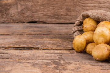 Young potatoes in a bag. Wooden desk table background.
