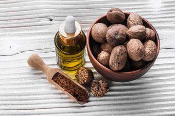 Fototapeta nutmeg essential oil on a gray wooden background obraz