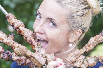 Young woman looking at camera and biting shish kebab