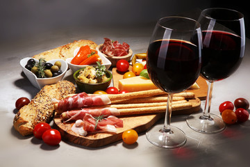 Italian antipasti wine snacks set. Cheese variety, Mediterranean olives, crudo, Prosciutto di Parma, salami and wine in glasses over stone grunge background.