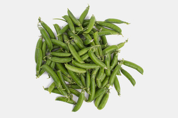 Pile of raw green organic snap peas. White isolated background.