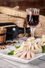 Traditional Georgian and Armenian cuisine. Georgian khinkali with a cherry on a white plate, on a wooden table in a restaurant. Wine on the table. Copy space, selective focus