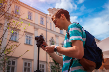 Portrait of happy young man, tourists with camera taking pictures of old city.