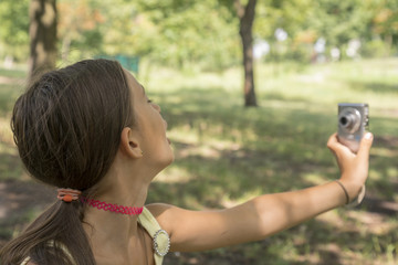 Little cute girl holding camera in hand and take a picture with selfie shot in park. beautiful eight-year-old girl in the park doing selfie.
