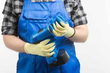 Close-up of builder men with screwdriver wearing gloves and blue overalls.