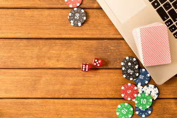 Online poker. Laptop, poker chips, dice, a deck of cards on a wooden table. Online casino concept