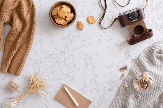 Hello Autumn flat lay background. Top view of workspace or office desk with vintage photo camera, sweater, cup of coffee, honey cookies, flowers and gold ears of wheat on textured white background