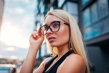 Young blonde businesswoman wearing glasses by business center in city. Fashion model. Formal style