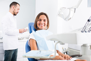 Girl is sitting satisfied after treatment in dental office