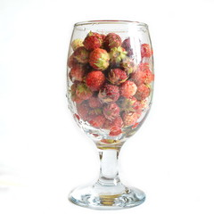 Glass transparent cup on a high leg filled with harvested fruit of ripe sweet fresh red wild forest field strawberry. White background