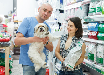 female with dog  choosing dry food with seller