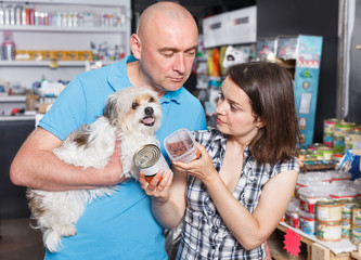 Couple with dog buying preserves for dogs