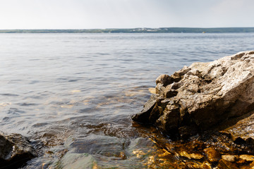 Big stones lie on sea beach. Coast. Nature background. Water with waves. Seascape