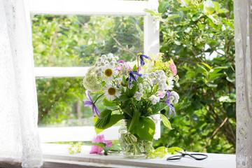 Bouquet of garden flowers on window