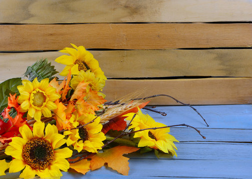 Autumn or fall still life arrangement of sunny yellow flowers, fall leaves and gourds and squashes on a two toned, natural and blue wooden background. Copy space