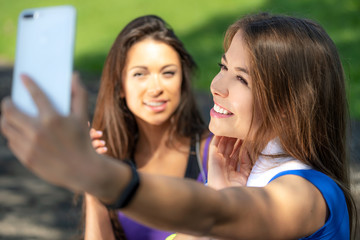 Millennials lifestyle concept - two sports girls taking a selfie and smiling after outdoors training on a sunny day.