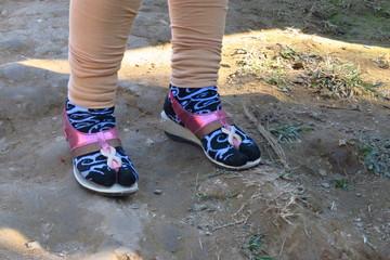 Feet of a nepalese woman wearing socks and sandals in the mountain village of Sekha, Khandbari, Nepal