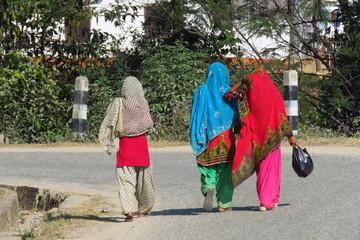 3 nepalese women wearing colorful clothes walking down a street, Khandbari, Nepal