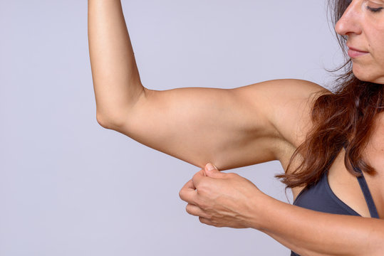 Woman stretching arm skin as she flexes muscle