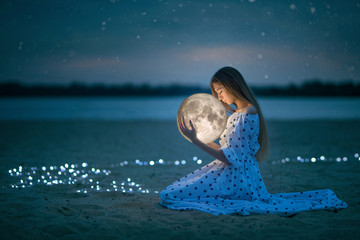 Beautiful attractive girl on a night beach with sand and stars hugs the moon, Artistic Photography Wall mural