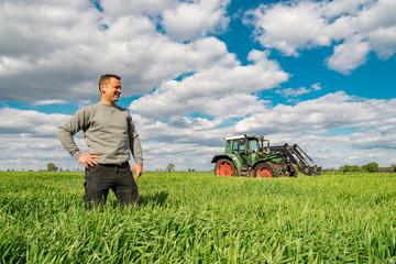 Unternehmerisches Handeln - Junger Landwirt betrachtet stolz seinen Getreidebestand