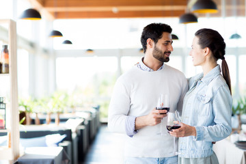 Young amorous and affectionate couple with glasses of red wine looking at one another in restaurant
