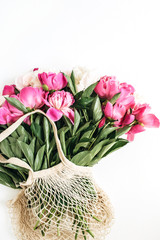 Minimal flat lay, top view of white and pink peonies flowers bouquet on white background.