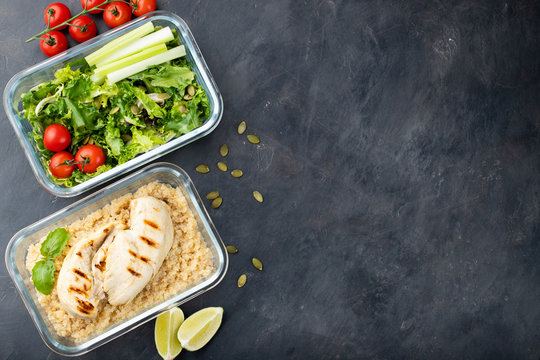 Healthy meal prep containers with quinoa, chicken breast and green salad overhead shot with copy space. Top view. Flat lay