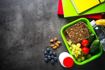 School lunch box and stationery on black background.