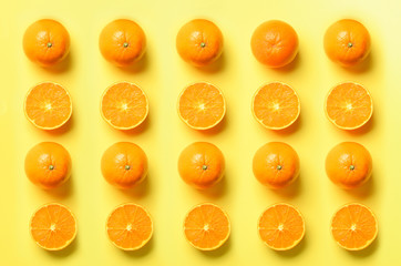 Fruit pattern of fresh orange slices on yellow background. Top view. Copy Space. Pop art design, creative summer concept. Half of citrus in minimal flat lay style.