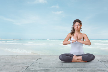 Young woman is meditating on the beach