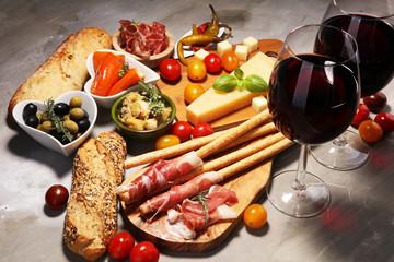 Italian antipasti wine snacks set. Cheese variety, Mediterranean olives, crudo, Prosciutto di Parma, salami and wine in glasses over stone grunge background.