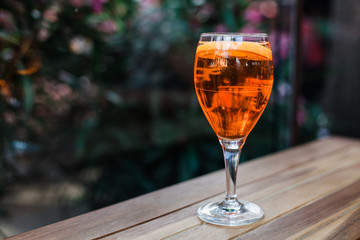 Aperol spritz cocktail in glass on wooden table on dark background in cafe