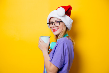 Young style girl in purple clothes and Christmas hat and cup on yellow background.  Clothes in 1980s style