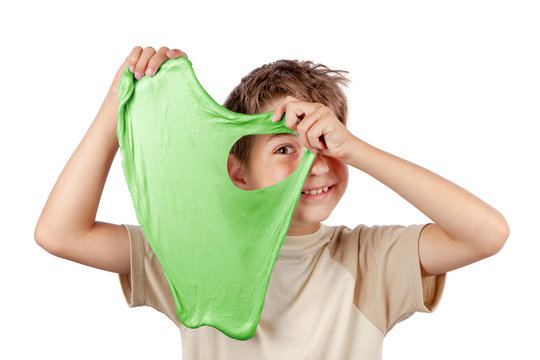 Cheerful boy holding a slime and looking throw its hole. Studio isolated on white background.