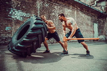 Two muscular athletes training. Muscular fitness shirtless man moving large tire other motivate him and hold big hummer in street gym. Concept lifting, workout training.