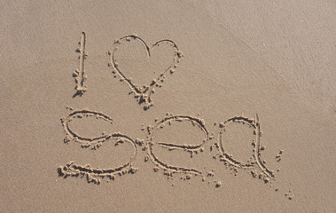inscription on the beach sand i love sea