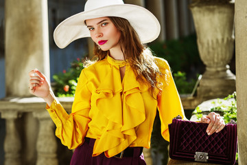 Outdoor fashion portrait of young beautiful woman wearing stylish white wide-brimmed hat, yellow blouse with jabot, holding violet quilted bag, posing in street, against old european architecture Wall mural