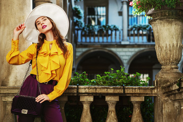 Outdoor fashion portrait of young beautiful woman wearing stylish white hat, yellow blouse with frills, holding violet velvet bag, posing in street, near old european architecture. Copy, epmty space