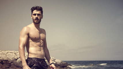 Handsome muscular young man standing on a beach, relaxed, shirtless