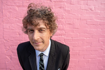 Fish-eye angle. Attractive forty-something man with kind eyes smiles while posing in dressy clothing in front of a vibrant pink wall.