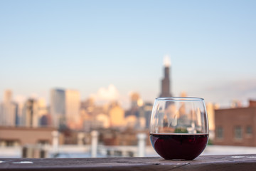 Glass of red wine ready to be enjoyed on a rooftop with a beautiful cityscape blurred in the background.
