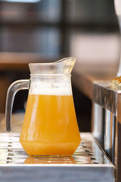beer pitcher with foam on a bar counter
