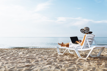 Freelancer girl working on vacation, in front of the beautiful sea, sitting with a laptop on the ocean, isolated place for text