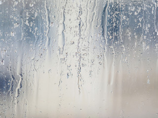 Rain drops on window glasses surface with blur building background. Natural Pattern of raindrops isolated on blur background.