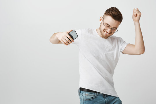Joyful pleased and carefree exciting handsome unshaven guy in glasses holding black smartphone dancing sliding on floor while listening music happily in wireless earphones over gray background